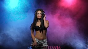 DJ Girl dancing with headphones and spinning discs in smoke stock video footage