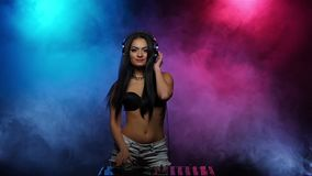 DJ Girl dancing with headphones and spinning discs in smoke. Slow motion stock video footage