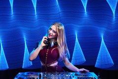 DJ girl on decks at the party. Beautiful DJ girl on decks at the party over blue led background Stock Photos
