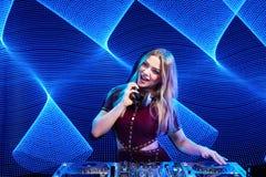 DJ girl on decks at the party. Beautiful DJ girl on decks at the party over blue led background Royalty Free Stock Photography