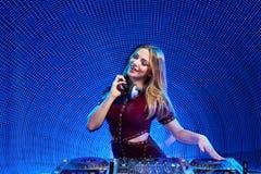 DJ girl on decks at the party. Beautiful DJ girl on decks at the party over blue led background Royalty Free Stock Image