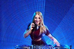 DJ girl on decks at the party. Beautiful DJ girl on decks at the party over blue led background Stock Image
