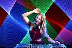 DJ girl on decks at the party. Beautiful DJ girl on decks at the party over colorful led background Stock Photo