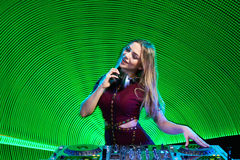 DJ girl on decks at the party. Beautiful DJ girl on playing mixing music on vinyl turntable at party over green led background Royalty Free Stock Photos