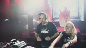 Dj girl and man mixing at turntable on party in nightclub. Spotlights. Spinning stock video
