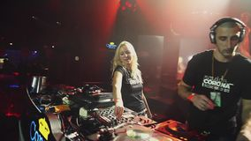Dj girl and man spinning, mixing at turntable on party in nightclub. Spotlights. stock footage