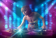 Dj girl mixing music in a club with blue and purple lights Stock Image