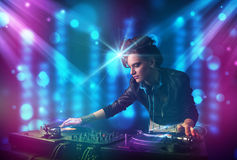 Dj girl mixing music in a club with blue and purple lights Royalty Free Stock Photography
