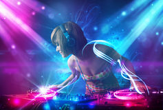 Dj girl mixing music with powerful light effects Stock Photo