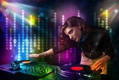 Dj girl playing songs in a disco with light show Royalty Free Stock Images