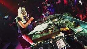 Dj girl spinning at turntable on party in nightclub. Dance. Go go girls on stage stock video footage