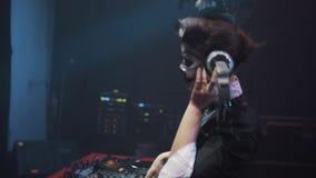 DJ in Halloween-kostuum en de make-up luisteren hoofdtelefoons spelend muziek en dans stock video