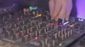 DJ hands pushing buttons on the mixing equipment. Night club atmosphere stock footage