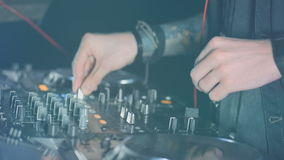 DJ hands turning volume control, creating music in the disco light. Close-up. HD. stock video footage