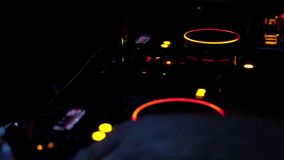 DJ hands under DJ music console, laptops and headphones in bright colors. Of light in night club bright red-blue background stock video footage