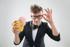 Dj handsome hipster eating donut from his cup on Royalty Free Stock Image