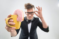Dj handsome hipster eating donut from his cup on Stock Photos