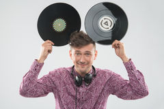 DJ having fun with vinyl record showing Mickey. Closeup portrait of excited young DJ with stylish haircut, bow tie having fun with vinyl record showing Mickey Stock Image