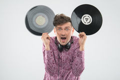 DJ having fun with vinyl record showing Mickey. Closeup portrait of excited young DJ with stylish haircut, bow tie having fun with vinyl record showing Mickey Stock Photo