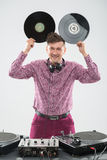 DJ having fun with vinyl record showing Mickey. Half-length portrait of excited young DJ with stylish haircut, bow tie having fun with vinyl record showing Stock Photos
