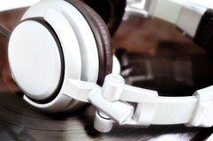 DJ headphones lying over old vinyl Stock Photos