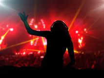 DJ with headphones at night club party. Under the spot lights and people crowd in background Royalty Free Stock Photo