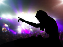 DJ with headphones at night club party. Under the spot lights and people crowd in background Royalty Free Stock Images
