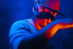 DJ with headphones playing mixing music at night party under the. Blue light. Fun, youth, entertainment and fest concept Stock Image