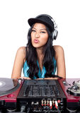 DJ with her gear. A young Asian female DJ making a funny face in front of a mixer and pair of turntables Royalty Free Stock Photo