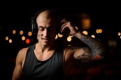 DJ in hoofdtelefoons voelt de muziek op de achtergrond van de lichten van de nachtclub stock foto