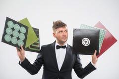 DJ im Smoking, das seine bereitstehenden Vinylaufzeichnungen zeigt Stockbild