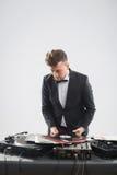 DJ im Smoking, das seine Vinylaufzeichnungs-Stellung betrachtet Stockbilder