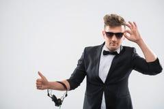 DJ im Smoking, das seinen oben bereitstehenden Daumen zeigt Stockbild