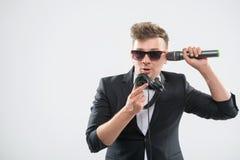 DJ im Smoking, das Spaß sprechend in Kopfhörer hat Lizenzfreie Stockfotografie