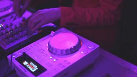 DJ in jacket spins turntable in night club. Stock footage stock footage