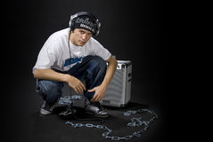 DJ with loudspeaker. A DJ with his portable loudspeaker equipment and chains, on black studio background royalty free stock image
