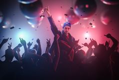DJ lub piosenkarz rękę up przy dyskoteki przyjęciem w klubie z tłumem ludzie Zdjęcia Stock