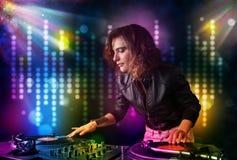 DJ-Mädchen, das Lieder in einer Disco mit heller Show spielt Lizenzfreie Stockfotos