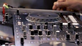 DJ mengt muzieksporen op audioconsole stock footage