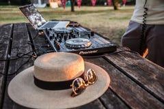 DJ, mezclador, sombrero y gafas de sol Partido del verano en la playa Lido Fotografía de archivo