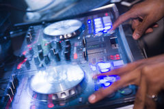 Dj mixer with dj hands make music with blue lights stock image