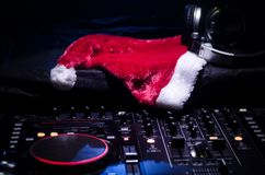 Dj mixer with headphones on dark nightclub background with Christmas tree New Year Eve. Close up view of New Year elements or symb stock image