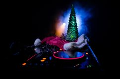 Dj mixer with headphones on dark nightclub background with Christmas tree New Year Eve. Close up view of New Year elements or symb Stock Photo