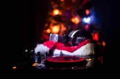 Dj mixer with headphones on dark nightclub background with Christmas tree New Year Eve. Close up view of New Year elements or symb Royalty Free Stock Photo