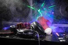 Dj mixer with headphones on dark nightclub background with Christmas tree New Year Eve. Close up view of New Year elements on a Dj stock images