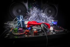 Dj mixer with headphones on dark nightclub background with Christmas tree New Year Eve. Close up view of New Year elements on a Dj stock photo