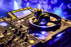 Dj mixer with headphones. At nightclub.  In the background laser light show Stock Photo