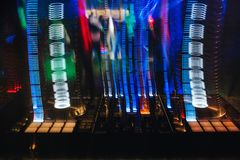 DJ mixer in a nightclub with glowing colored lights from controllers and buttons. In the nightclub stock photos