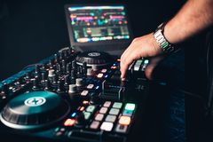 DJ mixes and manages music on professional contemporary music Board stock image