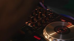 DJ mixes songs on equipment, hands closeup stock footage